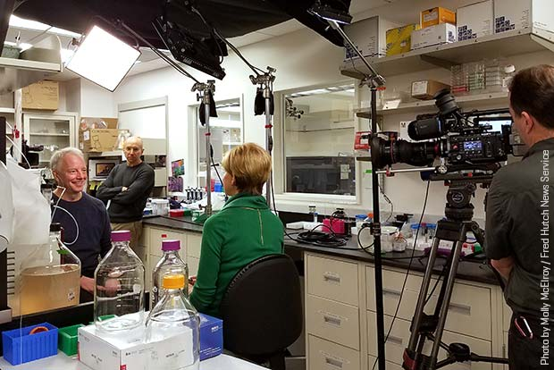 Dr. Jim Olson being interviewed in his lab by CBS correspondent Susan Spencer
