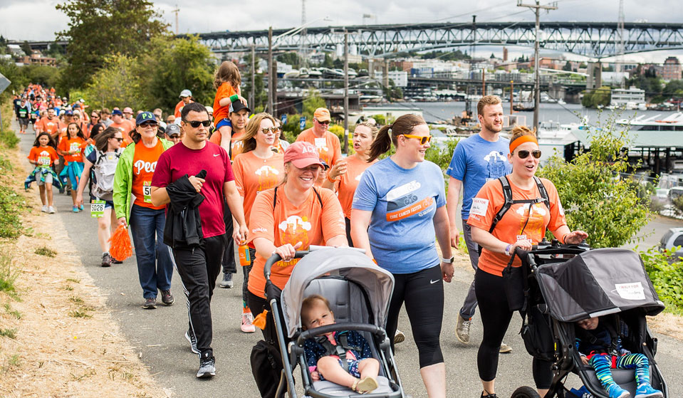 Many people, include two women with strollers, on the 5K walk