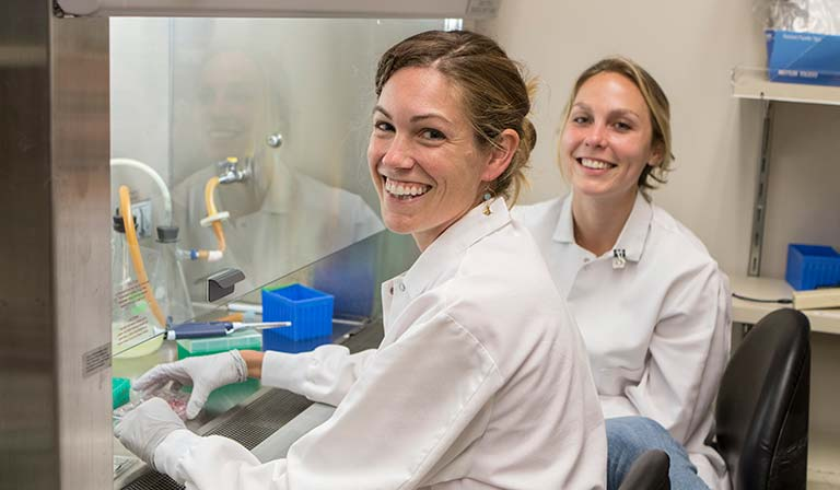 Two women in lab coats smiling