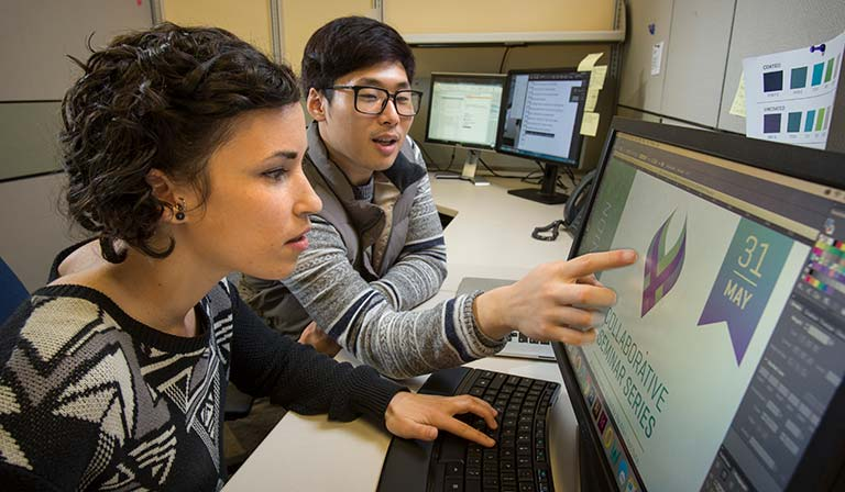 Interns studying a monitor