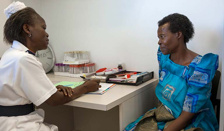 A nurse talks with a cervical cancer patient at the Uganda Cancer Institute, Fred Hutch UCI Center in Kampala, Uganda.