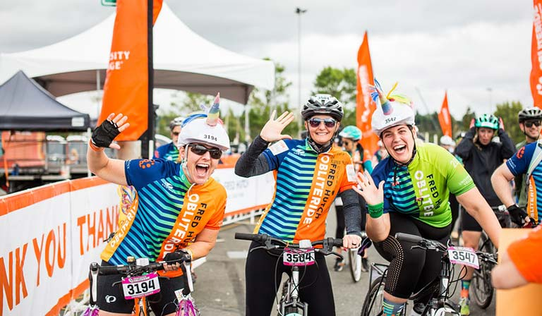 A group of cyclists pose for a photo at the Obliteride finish line