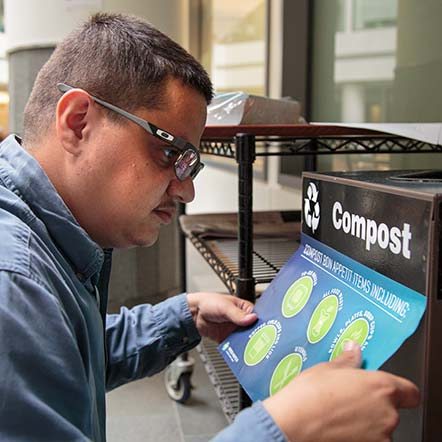 Igor Mandelman installs new signs on the recycle bins