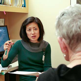Sylvia Lee speaking to patient at Seattle Cancer Care Alliance