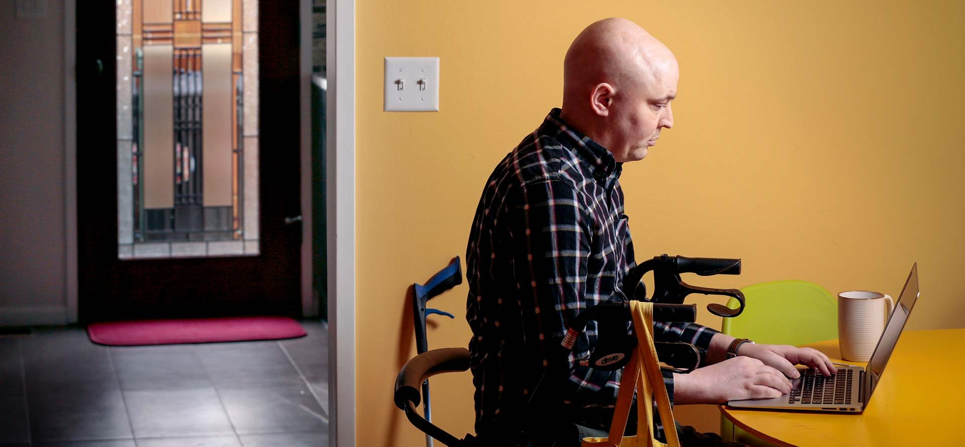 A cancer survivor on his laptop at home