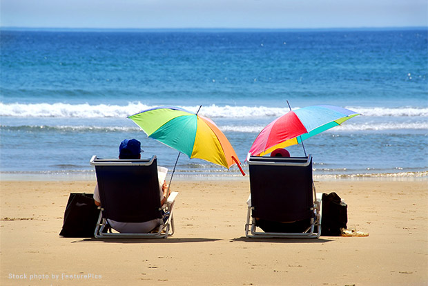 Two people sitting under sun umbrellas on a beach