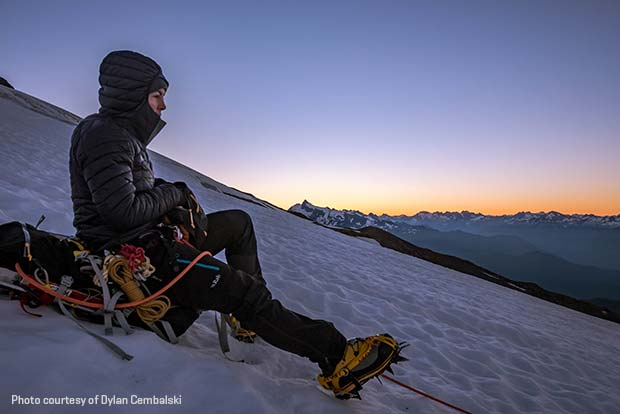 photo of climber sitting on side of snowy mountain