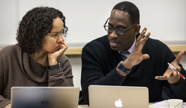 A woman and man talking and using laptops